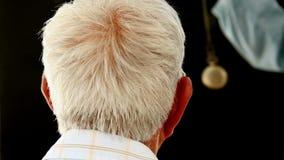 Senior man being hypnotized. In dark room stock footage
