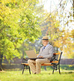 Senior man on bench and working on a laptop in a park Stock Images