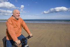 Senior man with bicycle on beach Stock Photo