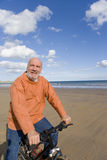 Senior man with bicycle on beach, portrait Royalty Free Stock Images