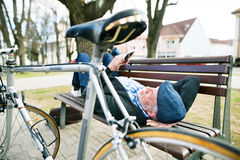 Senior man with bicycle in town, holding smart phone, texting Royalty Free Stock Images