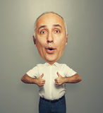 Senior man with big head showing thumbs up. Funny picture of excited senior man with big head showing thumbs up over dark background royalty free stock photography