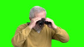 Senior man with binoculars, green screen. Old man in yellow sweater looking through binoculars, chroma key background. Expedition and exploration concept stock video footage