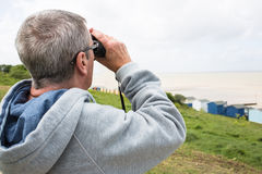 Senior man with binoculars Stock Images