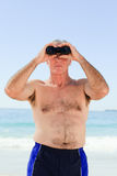 Senior man bird watching at the beach Royalty Free Stock Images
