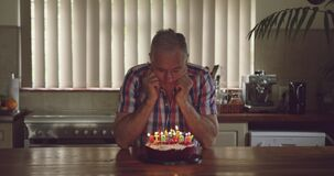 Senior man with a birthday cake at home