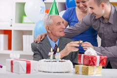 Senior man on birthday with his family. Family giving to father a present for his birthday Stock Photos