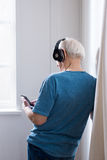 Senior man in black headphones using smartphone. Back view of senior man in black headphones using smartphone Royalty Free Stock Images