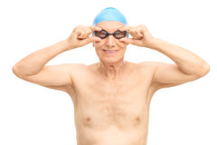 Senior man with black swimming goggles. Studio shot of a senior man with a blue swim cap and black swimming goggles isolated on white background Stock Photos