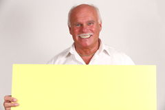 Senior man with blank sign. Portrait of mature or senior man with blank yellow sign; white studio background Stock Images
