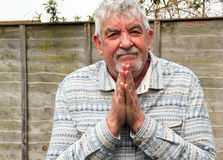 Senior man blessing with good fortune. A senior man looking towards the camera and holding his hands together and wishing good fortune, luck or health Stock Image