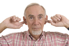 Senior man blocking ears. Studio shot of senior man with fingers in his ears, refusing to listen, in denial stock images