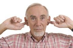 Senior man blocking ears. Studio shot of senior man with fingers in his ears, refusing to listen, in denial Stock Images