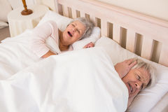 Senior man blocking out his wifes snoring Royalty Free Stock Photo