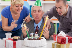 Senior man blowing candles Stock Images