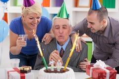 Senior man blowing candles Stock Photos
