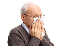 Senior man blowing his nose in a tissue Royalty Free Stock Photos