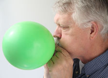 Senior man blowing up balloon Royalty Free Stock Images