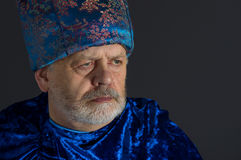 Senior man in blue oriental clothes against dark background Royalty Free Stock Photography