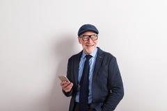 Senior man in blue shirt, jacket, eyeglasses and cap, holding sm Royalty Free Stock Photo