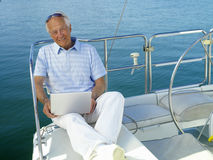 Senior man on boat with laptop computer, smiling, portrait Stock Photography