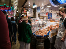 Senior man in boater and green jacket looks over fish counter, P Royalty Free Stock Photos