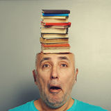 Senior man with books in the head. Surprised senior man with books in the head over grey background Royalty Free Stock Photos