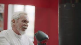 Senior man boxing combat bag at cardio training in healthy club. stock video