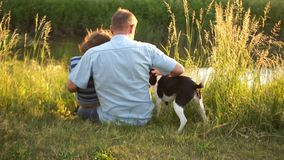 Senior man and a boy with his dog are sitting on the river bank. Friendly conversation, male conversation, sunset, happy