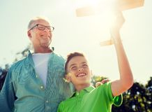 Senior man and boy with toy airplane over sky royalty free stock photo