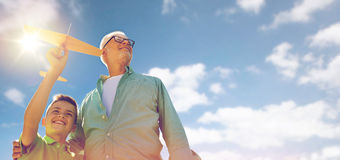 Senior man and boy with toy airplane over sky Royalty Free Stock Image