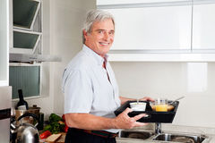 Senior man bringing breakfast tray. Happy senior man in kitchen bringing full breakfast tray Royalty Free Stock Photos