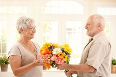 Senior man bringing flowers to wife Royalty Free Stock Photos