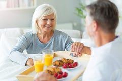 Senior man bringing his wife breakfast in bed. Senior couple enjoying breakfast in bed, smiling Stock Photos