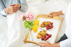 Senior man bringing his wife breakfast in bed. Senior couple enjoying breakfast in bed, smiling Royalty Free Stock Images