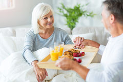Senior man bringing his wife breakfast in bed. Senior couple enjoying breakfast in bed, smiling Royalty Free Stock Photography
