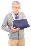 A senior man with a broken arm posing. Isolated against white background stock images