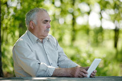Senior man browsing the internet on a tablet Royalty Free Stock Images