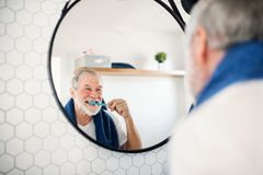 A senior man brushing teeth in bathroom indoors at home. Copy space. A senior man brushing teeth in bathroom indoors at home, looking in mirror. Copy space stock image