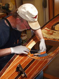 Senior man building wood strip kayak. Laying up hatch stop while working in well-lit shop Royalty Free Stock Image