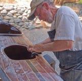 Senior man building wood strip kayak. Sanding deck while working outside Royalty Free Stock Image