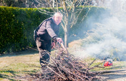 Senior man is burning dry branches Stock Photo