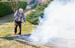 Senior man is burning dry branches Stock Photography