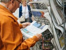 Senior man buy english press about United Kingdom general electi. PARIS, FRANCE - JUN 12, 2017: Senior man buying at press kiosk UK newspaper The Daily Telegraph Royalty Free Stock Photography