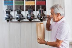 Senior Man Buying Coffee Beans At Grocery Store. Side view of senior man buying coffee beans from vending machine at grocery store royalty free stock images