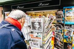 Senior man buying French newspaper Liberation at Parisian press. PARIS, FRANCE - MAR 15, 2018: Senior man buying French newspaper Liberation at Parisian press Royalty Free Stock Images