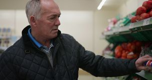 Senior man in the supermarket. Senior man is buying fruit and vegetables in the supermarket stock video footage