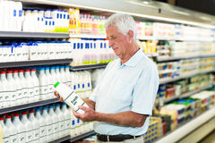 Senior man buying milk. At the supermarket stock photography