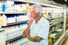 Senior man buying milk Royalty Free Stock Photography