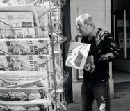 Senior man buying newspaper reporting handover ceremony presiden. PARIS, FRANCE - MAY 15, 2017: Senior man buys international newspaper reporting handover Stock Photo